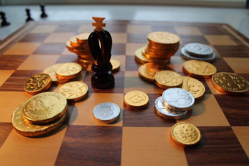 Chess king and chocolate coins on chessboard.