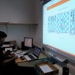 Adam Raoof in arbiter office of Southend Congress 2019, big screen shows top 3 boards.