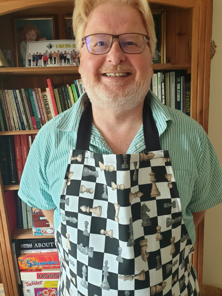 Graham Stuart, wearing chess themed apron
